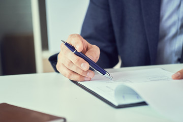 Businessman reading rental contract before making a deal. Corporate man with pen in hand working in modern office, signing business document on desk. close up.