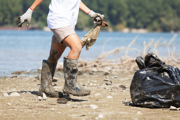 Collecting plastic waste at river or lake coast