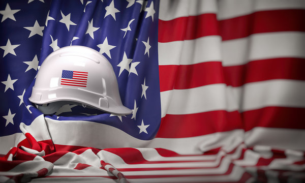 White hard hat laying over USA flag. Construction and employment in United States USA concept, Labor day
