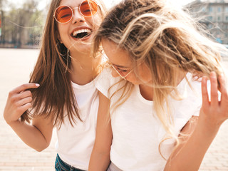 Portrait of two young beautiful blond smiling hipster girls in trendy summer white t-shirt clothes. Sexy carefree women posing on street background. Positive models having fun in sunglasses.Hugging Fotoväggar