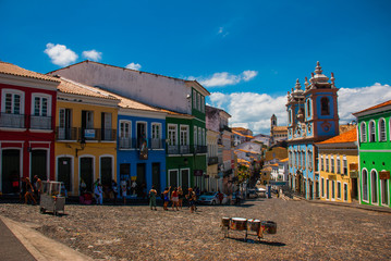 Historic city center of Pelourinho features brightly lit skyline of colonial architecture on a broad cobblestone hill in Salvador, Brazil