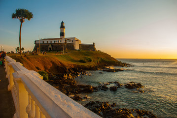 SALVADOR, BRAZIL: Sunset. Colorful sign stands in front of the colonial Farol da Barra lighthouse, the oldest in South America. Fototapete