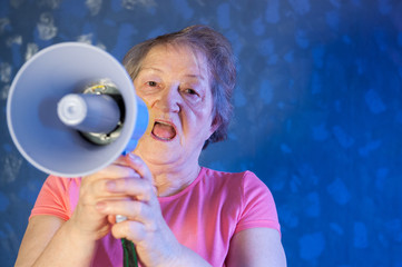 Beautiful senior woman is excited, euphoric, screaming with megaphone, sign of revolution and change, prompting other people to move, leader of personality at home. Elderly woman offers new products