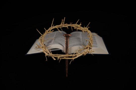 offene bibel mit dornenkrone und heiliger nagel