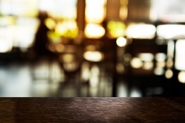top of black table wood with blur light in bar or restaurant with soft light background