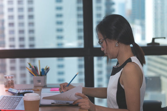 working woman sitting and work with document on desk in office building