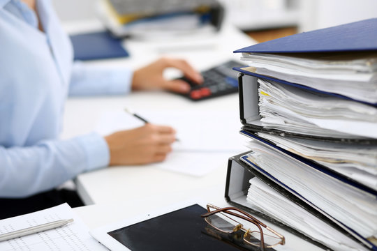 Binders with papers are waiting to be processed by business woman or bookkeeper back in blur. Internal Audit and tax concept