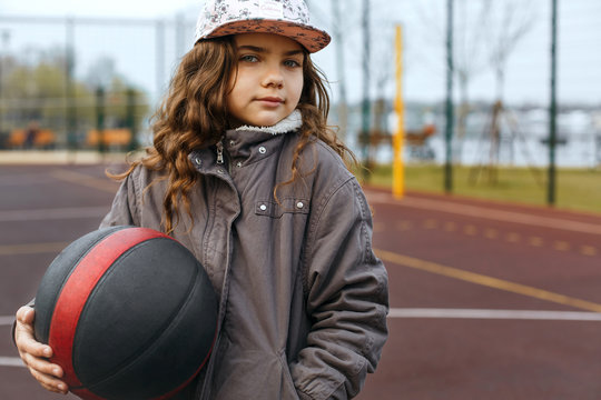 Little girl holding basketball ball at the street playground. Space for text