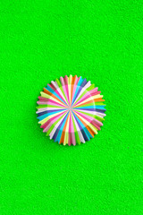 Rainbow colored paper baking cups for muffins and cupcakes on a green background minimal creative concept. Space for copy. Top view
