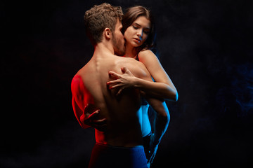 a young couple with rampant and animalistic sexuality. isolated black background . studio shot Wall mural