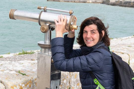 middle aged beautiful woman looking in telescope binoculars seaside ocean beach during tourism vacation