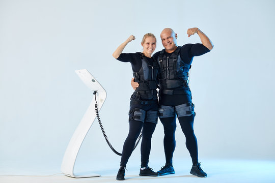 positive powerful couple in EMS suits with raised arms looking at the camera, isolated over white background. studio shot. body care, wellness, welbeing. full length photo