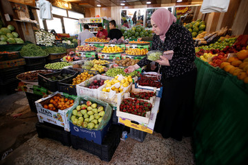 Venus Maythem Abbas buys fruit at a market during the holy month of Ramadan in Baghdad