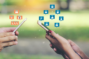 Hand holding smartphone with hologram or icon of set of social media on green background, Communication technology and Social media concept