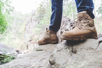 Hiking man with trekking boots on rock in forest Wall mural