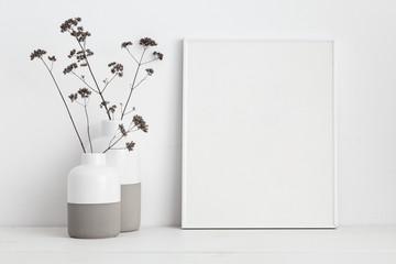 Frame and dry twigs in vase on book shelf or desk. Mockup. Fototapete