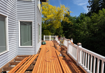 Outdoor red wooden cedar deck being remodeled with new floor boards freshly installed
