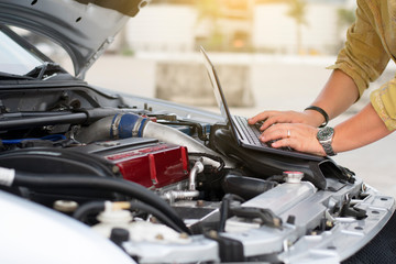 Technical man is using laptop to tuning racing car with engine bay view.