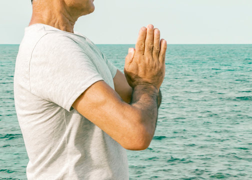 An adult man standing with palms in a gesture namaste by the sea. The concept of spirituality and self-awareness