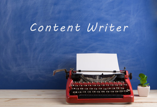 """writer's workplace - red typewriter on blue blackboard background with text """"content writer"""""""