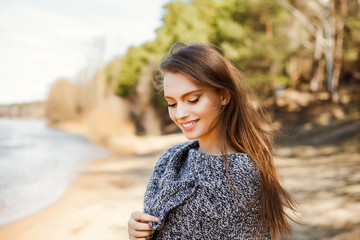 Natural beauty an attractive cute young girl, a portrait in a warm sweater on the river bank in early spring, a walk through the forest in nature