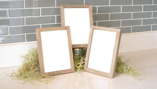 Three 5x7 natural wood picture frames with green moss and a tiled background