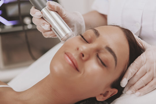 Charming young woman with smooth silky skin smiling, receiving microcurrent facial treatment by professional cosmetologist. Female client enjoying skincare therapy at dermatology clinic