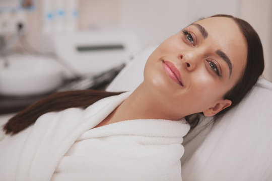 Close up of a happy healthy beautiful woman smiling, looking away joyfully, relaxing at spa center. Gorgeous young woman with flawless healthy skin resting after facial procedures, copy space