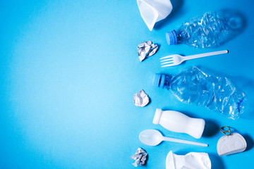 Plastic trash on blue background, eco concept image with copy space.
