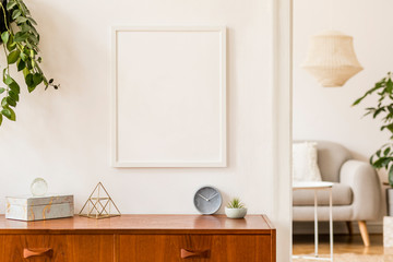 Stylish and retro space of home interior with white mock up frame, design sofa, furnitures, vintage cupboard with elegant accessories, plants and coffe table. Cozy home decor. Minimalistic concept.