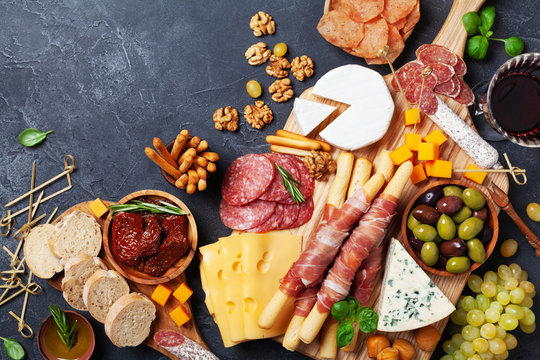 Italian appetizers or antipasto set with gourmet food on kitchen table top view. Mixed delicatessen of cheese and meat snacks with red wine.