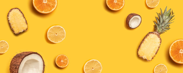 Tropical fruit flat lay with pineapple, oranges, lemon and coconut on a pastel background. Wall mural