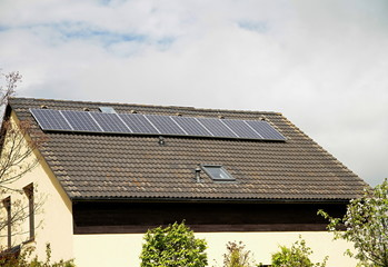 solar panels on house roof top with blue sky generating heat electrical power for the customer no people stock photo