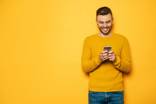 Handsome stylish young beard man in yellow with smart phone in hands is standing over yellow wall
