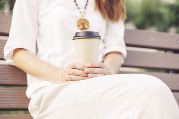 Unrecognizable woman sitting with takeaway paper cup of coffee.