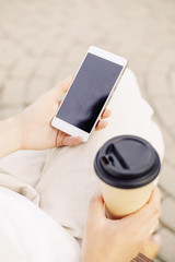 Unrecognizable woman with takeaway cup of coffee and smartphone.