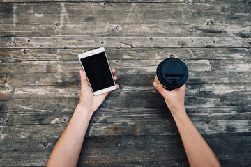 Female hands with smartphone and takeaway cup of coffee, pov.