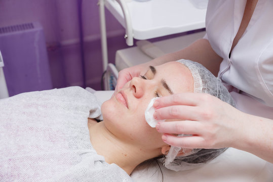 Beautician washes woman's face using cotton pads. Preparing for a cleaning face.