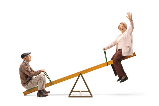 Senior man and woman waving and sitting on a seesaw