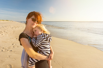 Junge Frau mit Kind auf dem Arm steht entspannt am Strand und genießt den Sonnenuntergang