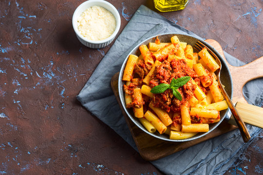 Delicious rigatoni pasta with italian tomato meat ragu sauce served in a pan on dark brown background. Traditional pasta dish concept. Home made lunch