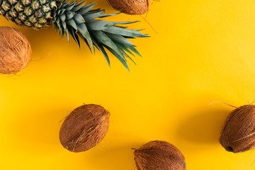 Summer fruit modern composition. Coconuts and pineapples on yellow background. Flat lay, top view, copy space