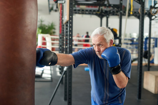 Male pensioner trains on a punching bag. Serious older man working out with punching bag at boxing hall. Sport training concept.