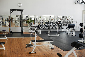 Fototapeten Fitness Gym interior with equipment. Modern fitness center with training equipment. Commercial gym interior design.