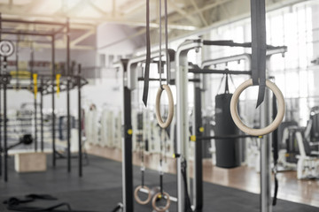 Set of gymnastic rings in gym. Sport accessories at fitness club. Crossfit gym interior.