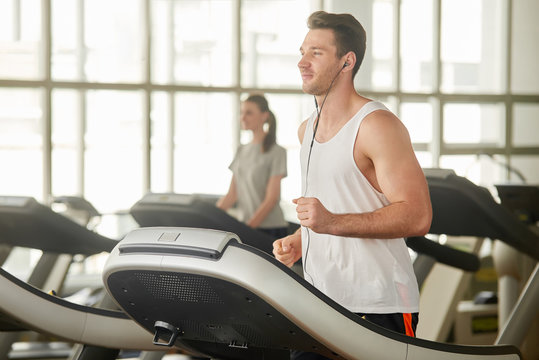 Young athletic man running on treadmill. Handsome muscular guy working out at gym and listening to music with headphones. Enjoy your lifestyle.