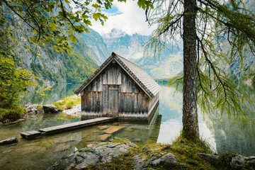Wall Mural - Idyllic view of traditional old wooden boat house at scenic Lake Obersee on a beautiful sunny day with blue sky and clouds in summer, Nationalpark Berchtesgadener Land, Bavaria, Germany