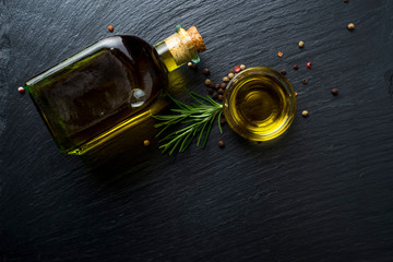 Virgin olive oil in a glass bottle and rosemary