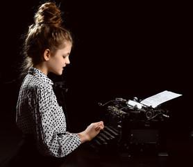 Pretty little girl kid typing letter on vintage typewriter keyboard machine on dark