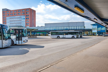 Buses parked near platforms with shelters at bus station